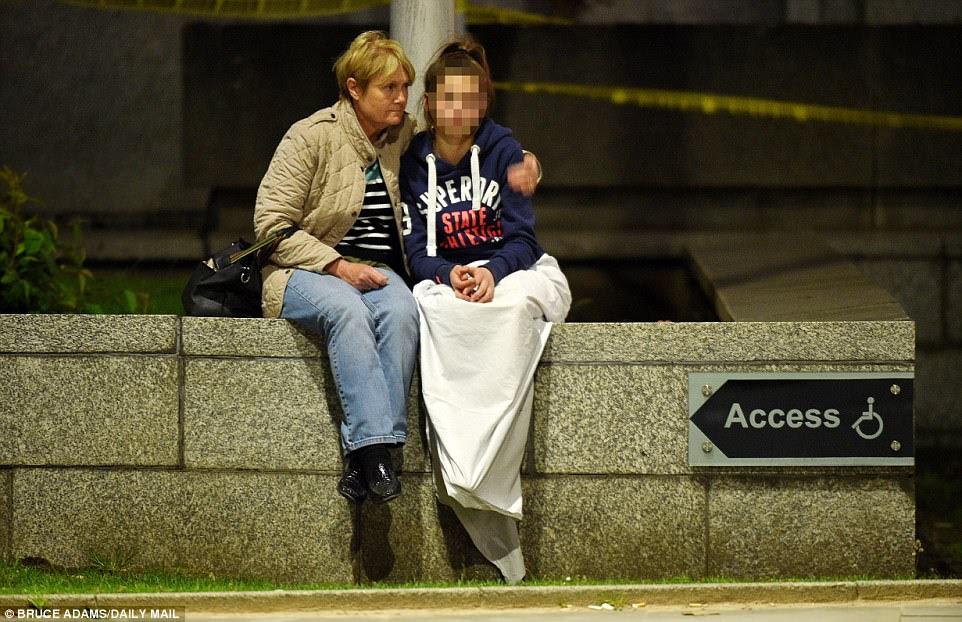 Uma mulher que senta-se em uma parede conforta uma menina envolvida em um cobertor branco.  Cenas angustiantes como esta foram uma lembrança do grande número de jovens no local