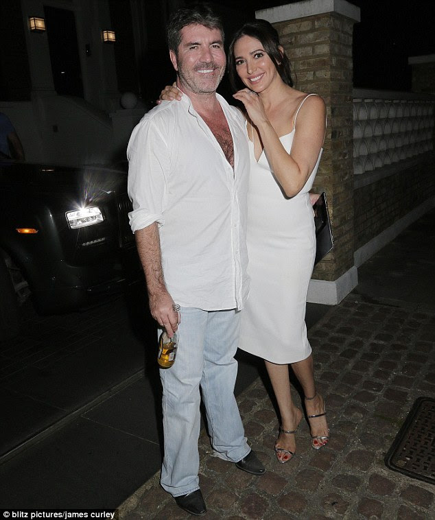 Perfect pairing: Simon Cowell arrived at his record label's party on Monday night alongside his stunning partner Lauren Silverman