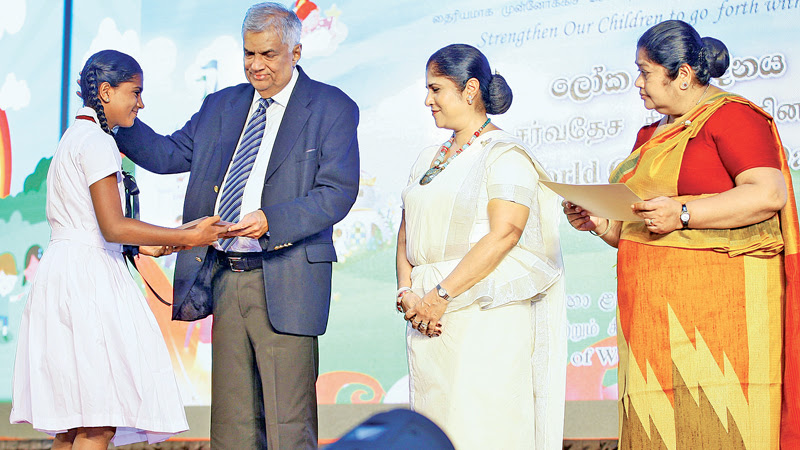 The National Ceremony to mark World Children's Day was held at Temple Trees under the patronage of Prime Minister Ranil Wickremesinghe yesterday. (October 1). Here, Prime Minister Wickremesinghe distributing prizes and certificates among a group of children who had displayed special skills and talents. Women's and Children Affairs Minister Chandrani Bandara and Women's and Children's Affairs Ministry Secretary Asoka Alawatte were also present on the occasion. Picture by Hirantha Gunathilake