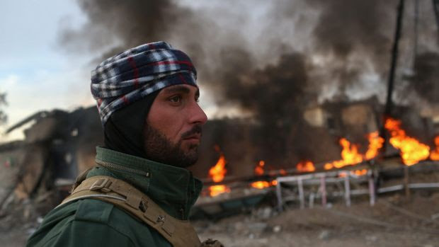 A Kurdish Peshmerga soldier passes by tires set on fire in Sinjar, Iraq, days before by Islamic militants late last year.