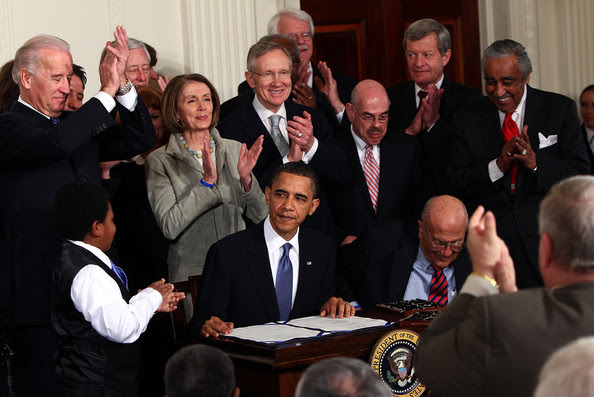 U.S. President Barack Obama (C) is applauded after signing the Affordable Health Care for America Act during a ceremony with fellow Democrats in the East Room of the White House March 23, 2010 in Washington, DC. The historic bill was passed by the House of Representatives Sunday after a 14-month-long political battle that left the legislation without a single Republican vote.