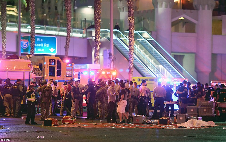 What appears to be a body under a sheet lies in front of swarms of police and rescue personnel at the intersection of Las Vegas Boulevard and Tropicana Ave