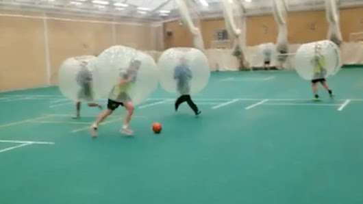 Cricketers play football wearing giant bubbles – video