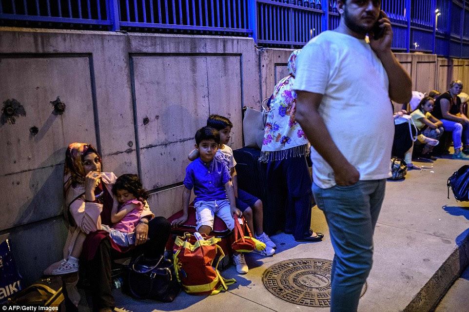 Famílias esperar fora do terminal com a sua bagagem após todos os planos foram cancelados depois do ataque, em que três homens armados abriram fogo e detonaram coletes suicidas