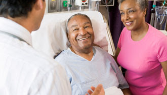 : Image of a man in a hospital bed talking with his doctor about how to prevent DVT after surgery.