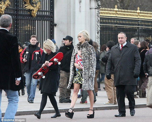 Blending in: Fearne walks with her entourage among the tourists in front of the Buckingham Palace gates