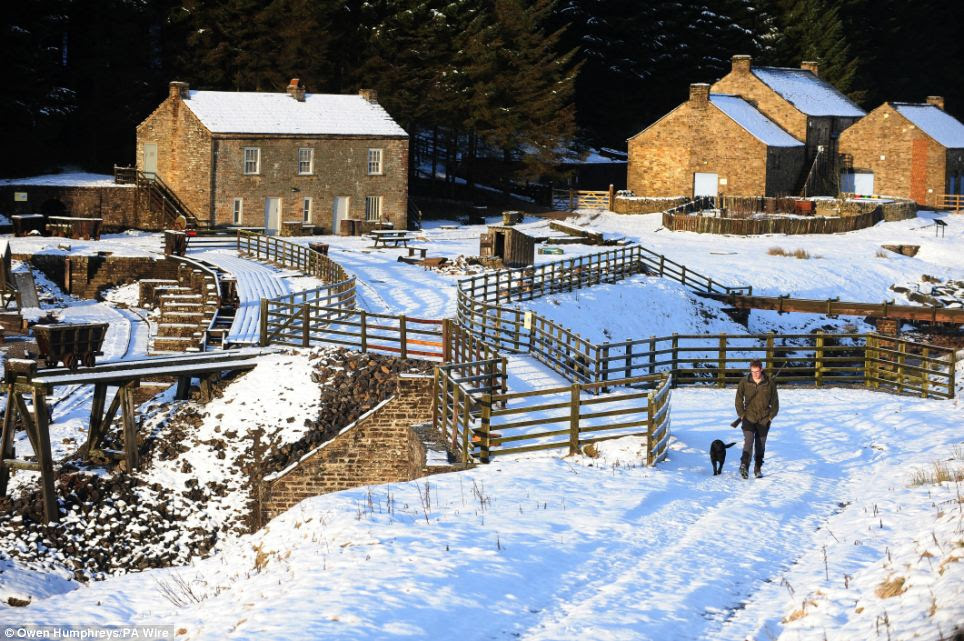 A man walks his dog through the snow at Kilhope, in County Durham