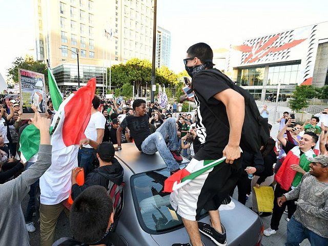 Protesters climb atop a car stopped in traffic as a crowd marches near the venue where Republican presidential candidate Donald Trump was speaking during a rally in San Jose, California on June 2, 2016.  Protesters who oppose Donald Trump scuffled with his supporters on June 2 as the presumptive Republican presidential nominee held a rally in California, with fistfights erupting and one supporter hit with an egg. / AFP / JOSH EDELSON        (Photo credit should read JOSH EDELSON/AFP/Getty Images)
