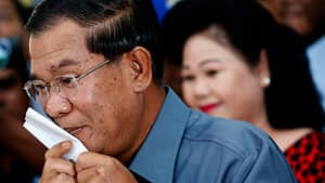 Cambodia's Prime Minister Hun Sen kisses his ballot before casting it in the general elections at a polling station in Kandal province on Sunday.