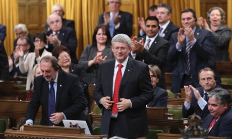 Canada's prime minister, Stephen Harper, stands to vote in favour of a government motion to participate in US-led air strikes against Islamic State militants in Iraq.