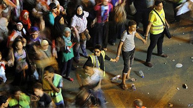 Voluntários usando coletes amarelos protegem mulheres na praça Tahrir (Foto: AP)