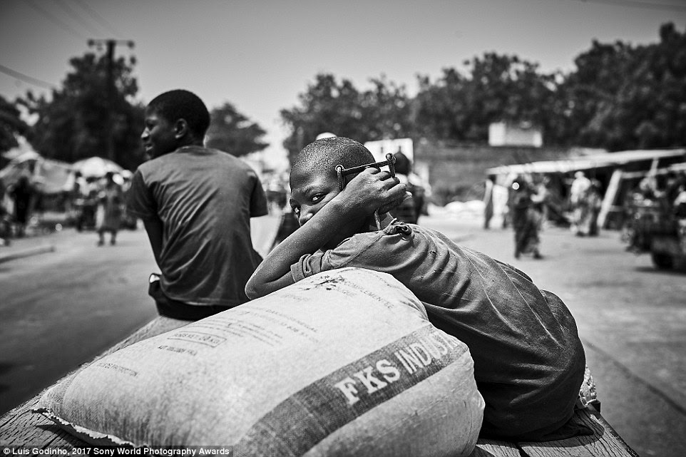 A young boy in Senegal pictured travelling aboard a carriage guarding a bag of flour, which will be used to make bread