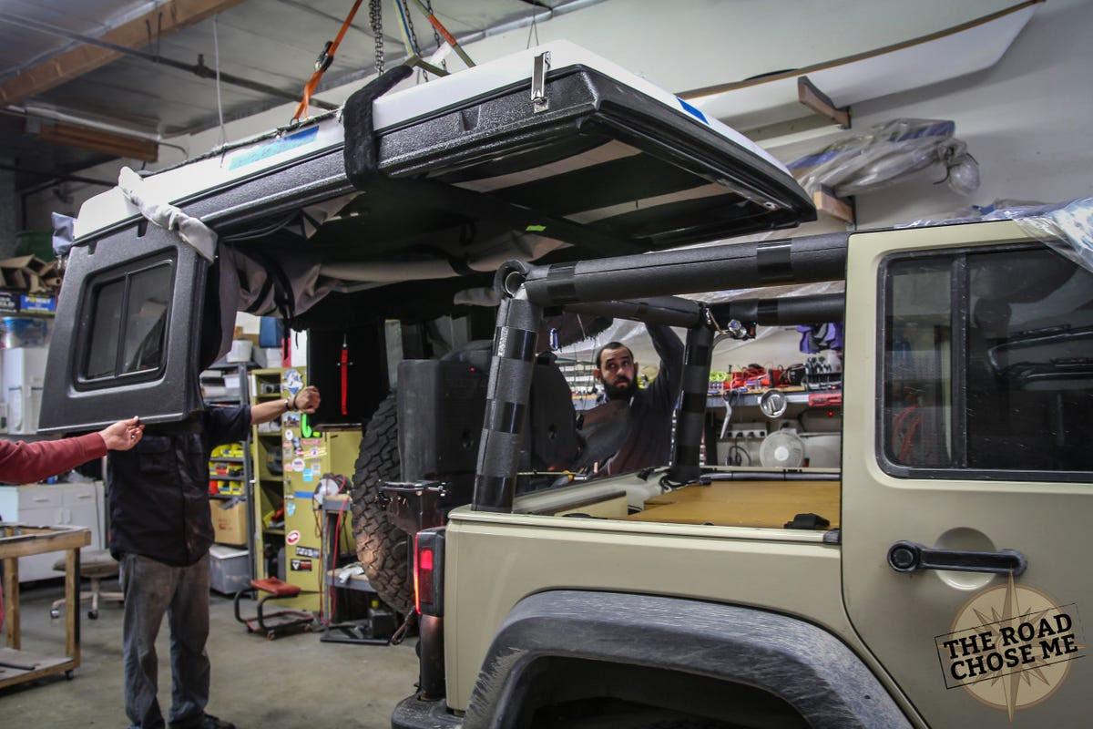 I had a pop-up roof installed by a company called Ursa Minor. This replaces the stock Jeep hard top, and pops open. Normally it's a bolt-on to a stock Jeep, but my modified roll bar meant we could open it right up, so I can stand up and walk around in the back of the Jeep for massive interior living space.