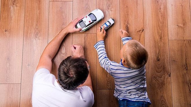 Padre e hijo juegan con coches de juguete