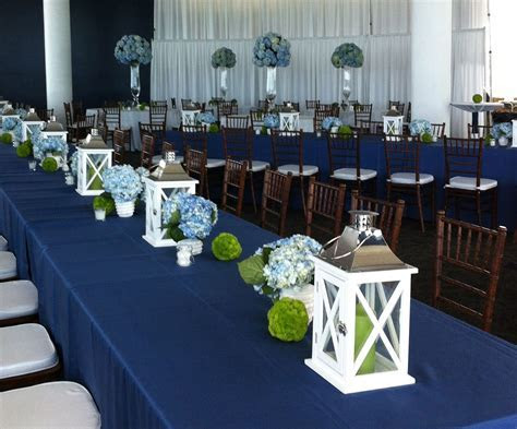 White lanterns line long tables with navy table cloths