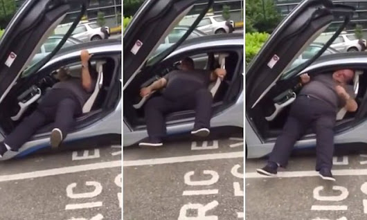 Friends laugh as man struggles to get out of low-slung BMW