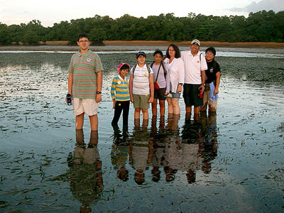 Dr Yaacob Ibrahim, Minister for the Environment and Water Resources, Singapore, with family and friends crossing the seagrass lagoon.