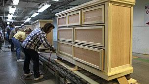 trabajadores en una fábriac de muebles estadounidense