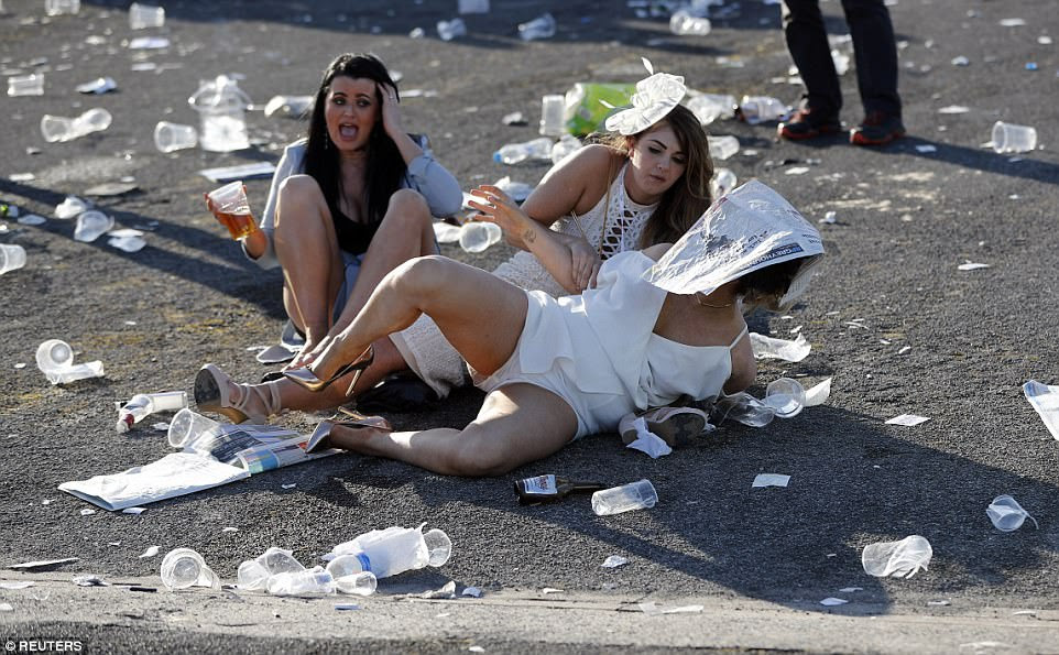 These female racegoers were spotted rolling around on the floor at Ladies Day - one even ended up with a newspaper covering her head