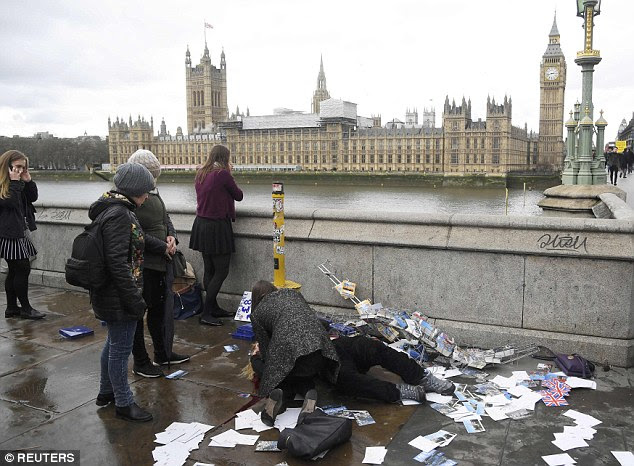 An injured woman is assisted after a man drove a 4x4 into pedestrians along Westminster Bridge on Wednesday afternoon