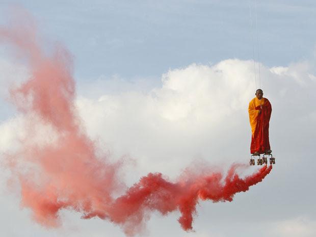 Suspenso por fios, o artista chinês Li Wei realiza uma performance no céu de La Villette, em Paris, nesta terça-feira (20). Li Wei nasceu em 1970, Hubei, na China é um artista contemporâneo de Pequim. (Foto: Francois Mori/AP)