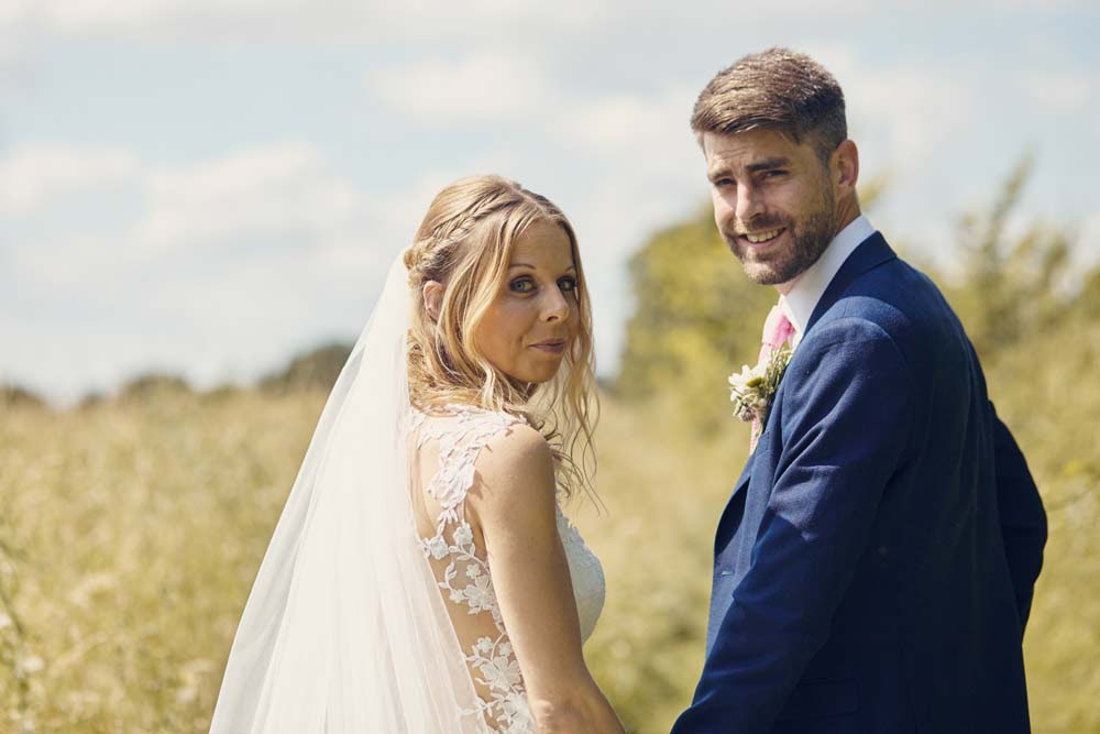 Bride and groom look over shoulder at Wingfield Barns, Norfolk- www.helloromance.co.uk
