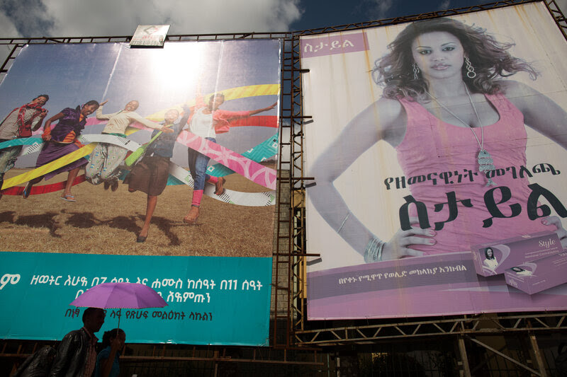 A couple walks by billboards advertising family planning methods in Addis Ababa.