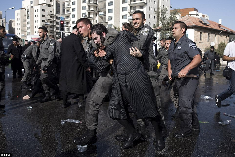 Israeli Border Police arrest an Ultra-Orthodox Jewish demonstrators blocking a main junction as they protest against army recruitment in Jerusalem