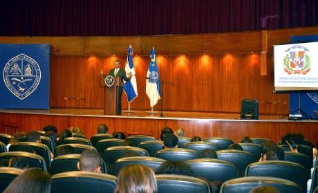 imagen Conferencista de pie en podium se dirife a estudiantes sentados