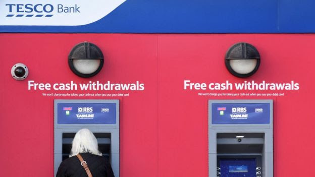 Woman withdrawing cash at Tesco Bank ATM