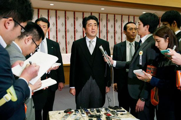 Japan's Prime Minister Abe speaks to media after visiting the controversial Yasukuni Shrine to pay tribute to the war dead, in Tokyo