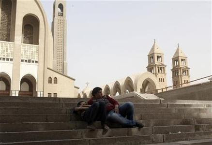 Coptic Christians sleep and relax on stairs inside Cairo's main Coptic cathedral after Sunday's clashes with Muslims in Cairo, April 8, 2013. REUTERS-Asmaa Waguih (EGYPT - Tags: RELIGION POLITICS CIVIL UNREST)