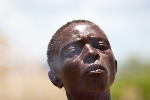 Tonga woman exhaling smoke with eyes closed, near Binga, Zimbabwe