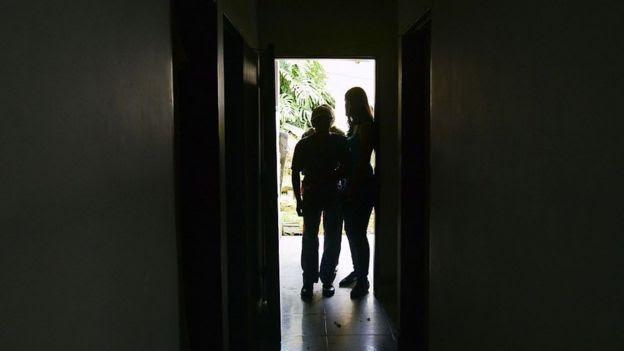 Anciando con Alzheimer siendo guiado por otras dos personas.