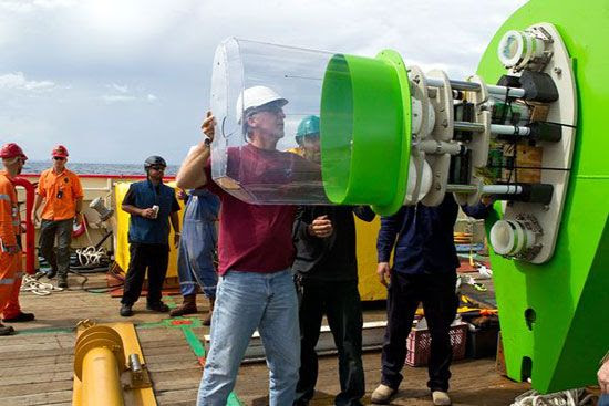 James Cameron fits a casing onto an instrument package atop the Deepsea Challenger submersible, which took him to the bottom of the Mariana's Trench on March 26, 2012 (Guam Time).