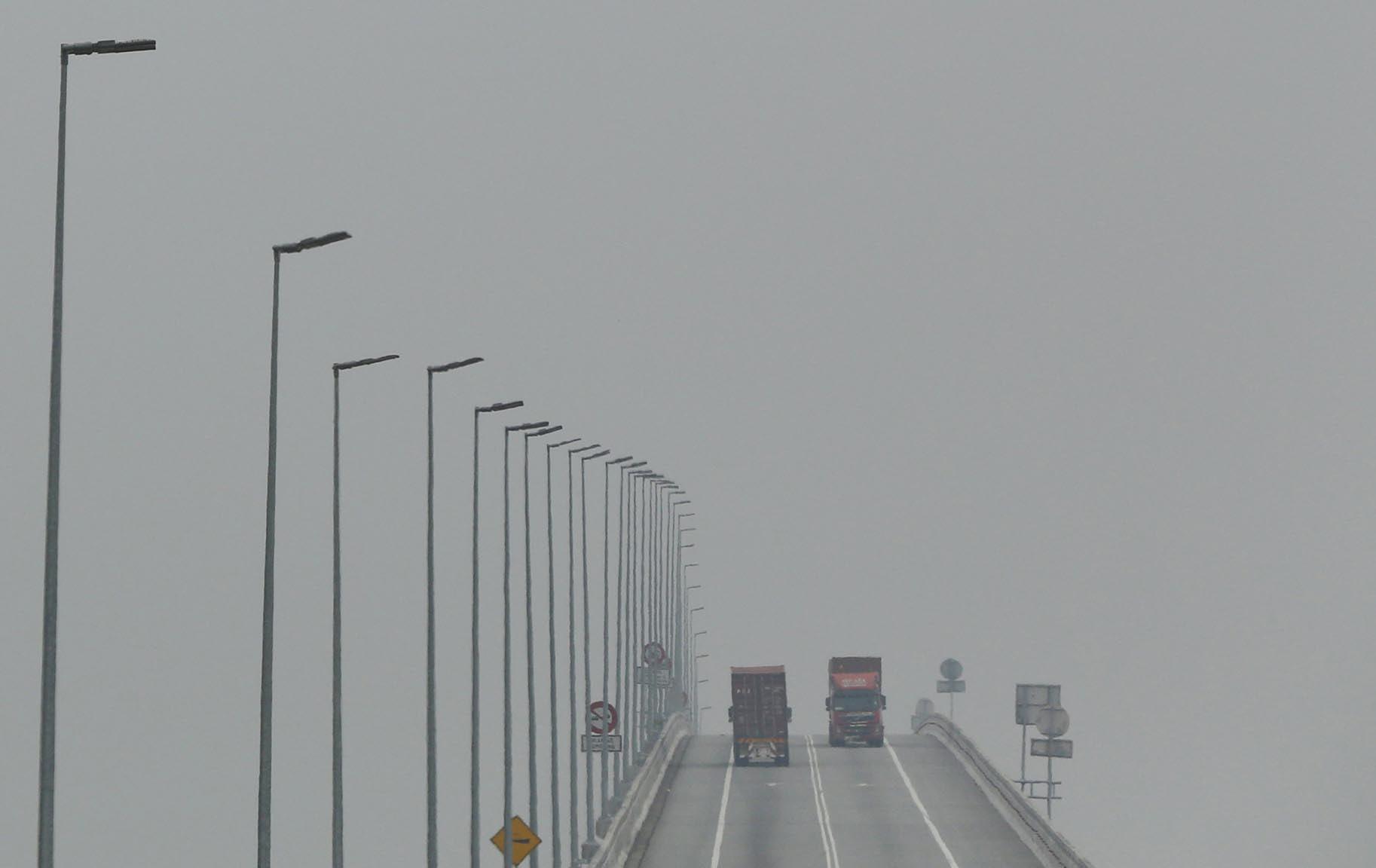 Lorries cross a bridge shrouded in haze in Klang, Malaysia