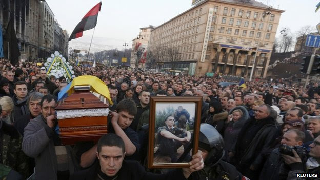 People carry the coffin of an anti-government protester who was killed during Thursday's clashes with riot police, in Independence Square in Kiev on 21 February 2014.