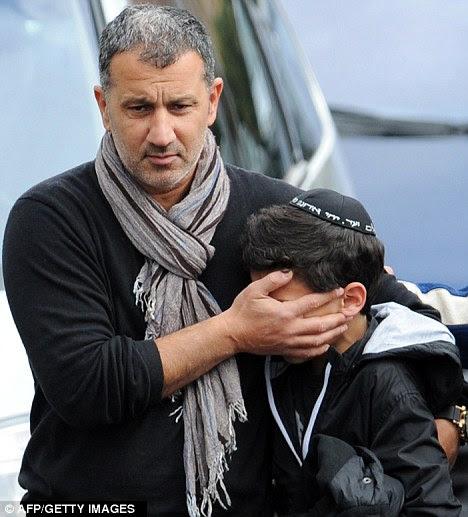 Horror: Een kind wordt getroost door een man naar schietpartijen deze week in Frankrijk