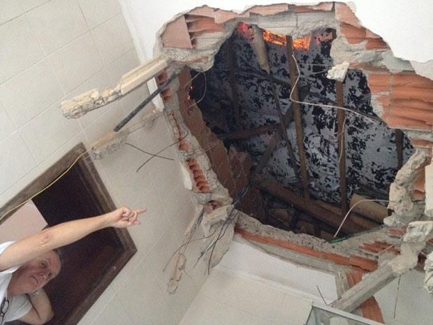 Quase um mês depois, Ricardo Fuchs aponta para buraco no teto do banheiro por onde passou rotor, que destruiu detalho e estrutura de concreto até parar no piso (Foto: Kleber Tomaz / G1)