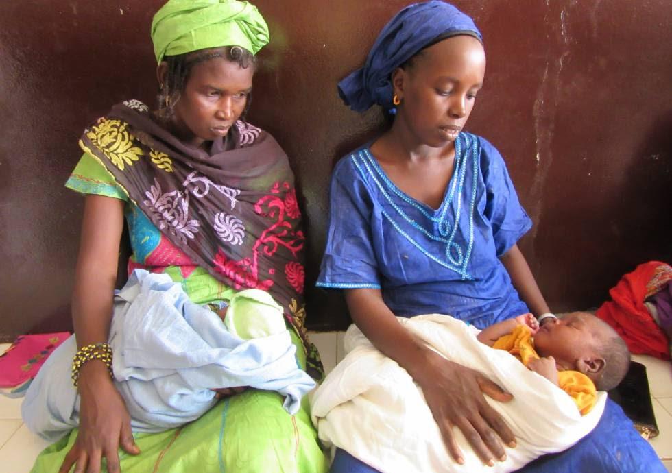 Dos jóvenes madres observan al bebé de una de ellas, que sufre de un problema cutáneo derivado de la desnutrición, en la sala de espera de Pediatría del hospital regional de Ndioum. La deshidratación y la diarrea suelen ser patologías asociadas, así como los problemas en la piel.