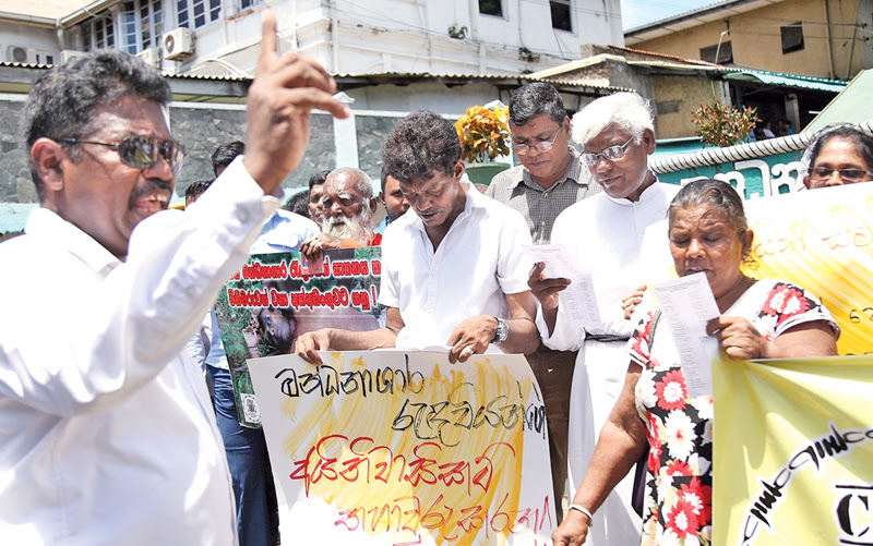 Activists in front of the Welikada Prison demanding justice for prisoners while Prison Reforms Minister D.M Swaminathan makes a statement to the media explaining the Government stance yesterday. Pictures by Rukmal Gamage