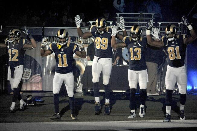 Members of the St. Louis Rams raise their arms as they walk onto the field on Sunday, Nov. 30, 2014, before a football game against the Oakland Raiders.
