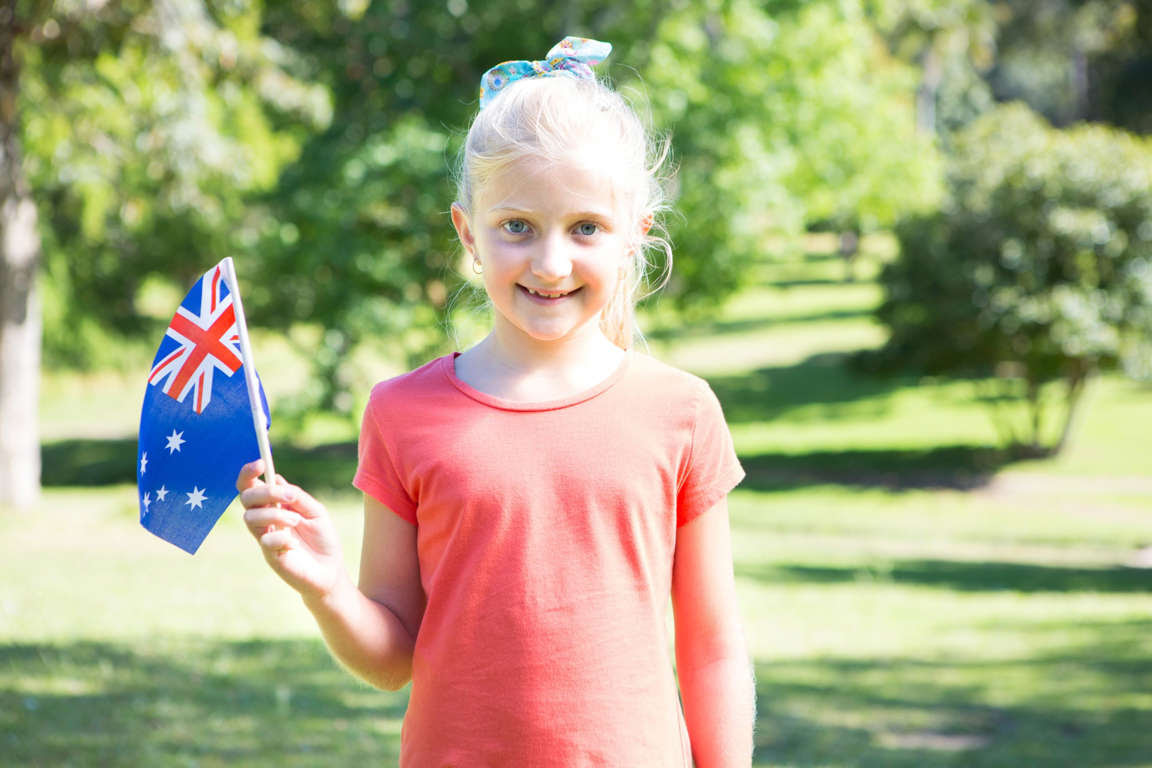 Little girl waving australian flag on a sunny day