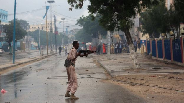 A Somali government soldier takes position during gunfire after a suicide bomb attack outside a hotel in Somalia's capital Mogadishu on 25 June