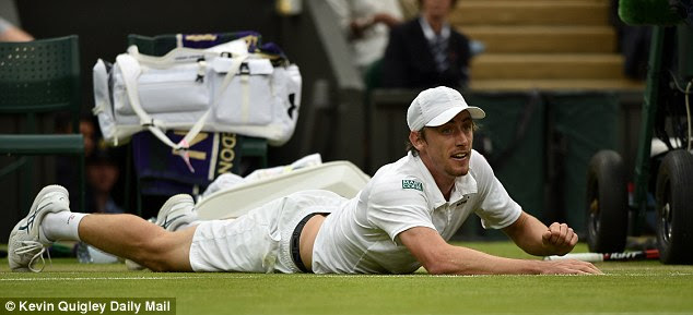 Millman loses his footing and falls to the floor in a rally with Murray during the third set but was unhurt