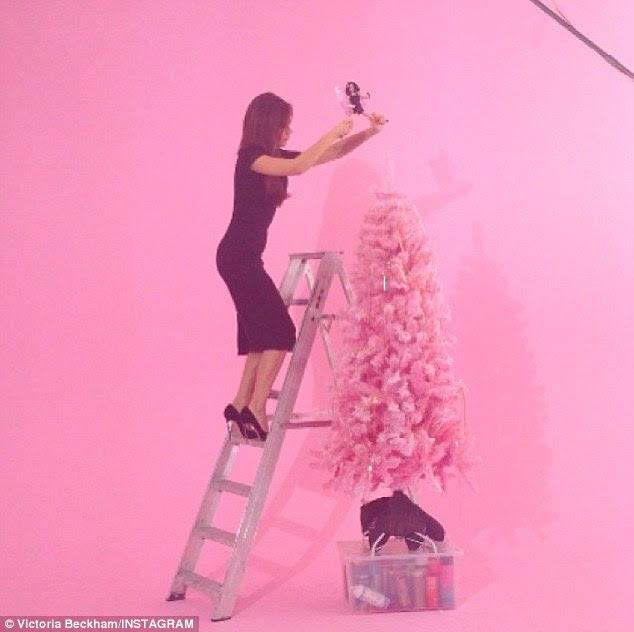 Careful: Victoria Beckham decorates a pink Christmas tree with a Posh Spice figurine