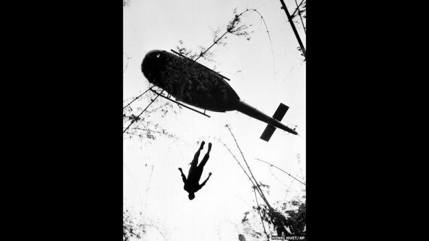 El cuerpo de un paracaidista estadounidense muerto en combate en la selva cerca de la frontera con Camboya es elevado para ser transportado en helicóptero. 14 de mayo de 1966. Foto de Henri Huet/AP.