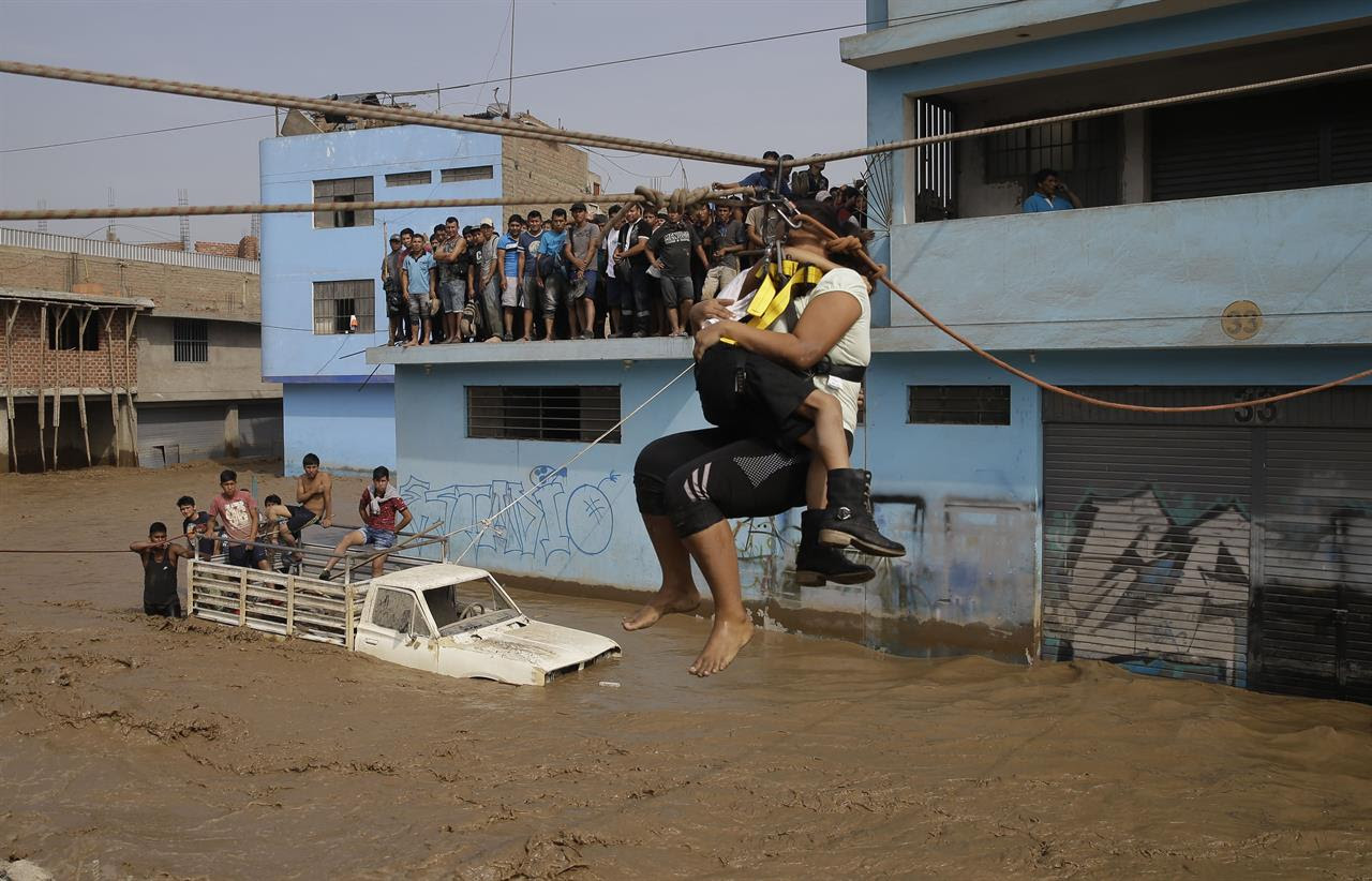 A mother holds her daughter as they are pulled across flood waters in a zip line harness in Lima, Peru, Friday, March 17, 2017. Intense rains and mudslides over the past three days have wrought havoc around the Andean nation and caught residents in Lima, a desert city of 10 million where it almost never rains, by surprise.