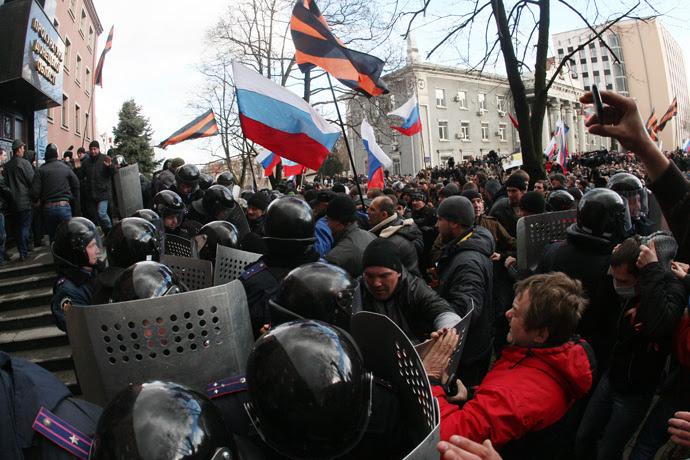 Les militants pro-russes brandissent des drapeaux russes et des drapeaux aux couleurs du ruban de Saint-Georges, une décoration militaire russe, au moment où ils prennent d'assaut le bureau du procureur dans la ville ukrainienne de Donetsk le 16 Mars 2014 (AFP Photo / Alexander Khudoteply)