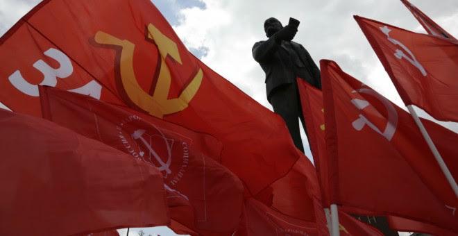 Miembros del Partido Comunista ondean sus banderas junto a una estatua de Vladimir Lenin en Simferopol, capital de Crimea. - AFP